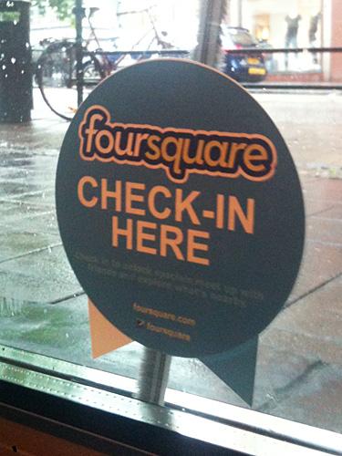 Man uppmanas att checka in på McDonald's på Foursquare av en klisterlapp på rutan